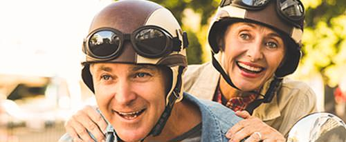 older couple excitedly riding a moped