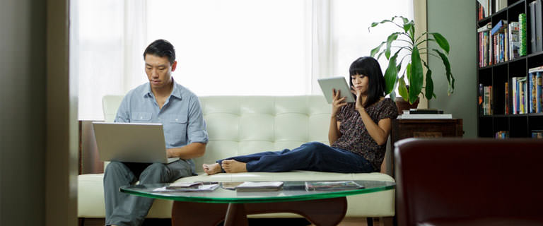 couple using tech devices on a couch